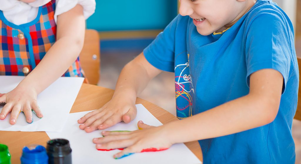 Cute preschool children painting with their palms at kindergarten being creative for their school tea towel fundraiser